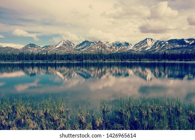 Jagged snowy mountain peaks with snow on the top reflected in shallow river during early summer.