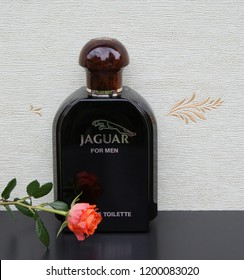 Jaguar for Men Eau de Toilette big perfume bottle in front of the satin wallcovering Elysee decorated with a rose Kassel Germany 09.15.2018 Jaguar for Men is a men's fragrance, launched in 1988