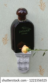 Jaguar for Men, Eau de Toilette, large perfume bottle on an antique wall console with ornament decorated with a rose Kassel, Germany, 10.03.2018: Jaguar for Men is a men's fragrance, launched in 1988