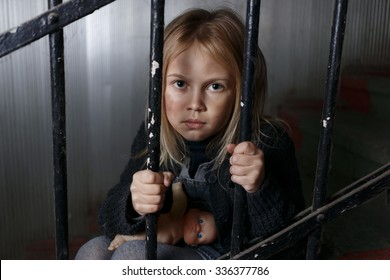 In jail of destiny. Poor sad hopeless girl sitting on the staircases and holding handrail while feeling depressed
