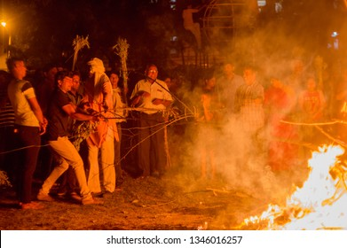Jaipur, India - 20th Mar 2019 : People pulling out a stick denoting the mythical figure of Prahlad from holika dahan bonfire. This represents the killing of the demon Holika by god vishnu while saving