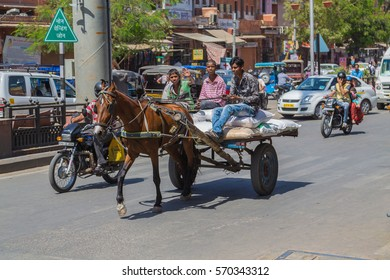 JAIPUR, INDIA - 23RD MARCH 2016: Young men riding a horse and cart in central Jaipur during the day.