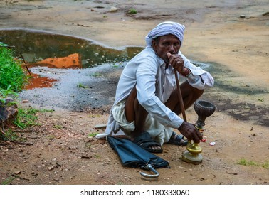 Jaipur /India - August 12, 2012:  Indian male smoking a hookah while squatting on the ground in a rural village near Jaipur, India.