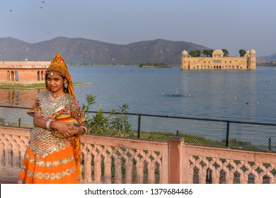Jaipur, India - February 01, 2019: Girl in traditional dress for taking pictures front of Jal Mahal, Water Palace in Man Sagar Lake in Jaipur. Rajasthan