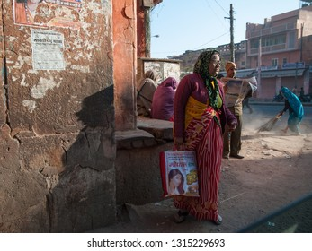 JAIPUR, INDIA - FEBRUARY 2, 2011: Urban scene with a woman sweeping a dusrty street in Jaipur. Jaipur is the largest city in Rajasthan with a population of 3-4 million.