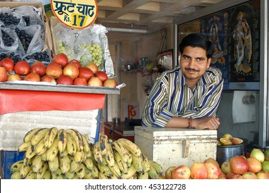 JAIPUR, INDIA - FEBRUARY 24, 2006: Smiling seller of fruits and vegetables at a market stall in the city of Jaipur