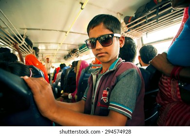 JAIPUR, INDIA - JAN 19: Unidentified kid in sunglasses driving inside a city bus with crowd of passengers on January 19, 2015 in Rajasthan. Jaipur, with popul. 6,664000, is a capital of Rajasthan