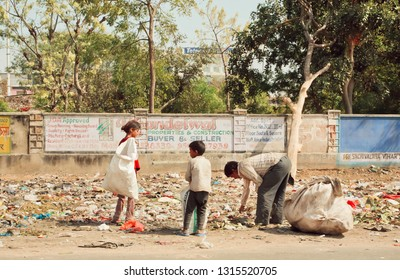 JAIPUR, INDIA - JAN 21: Garbage on dirty street and poor family collecting rubbish for money, food and recycling on January 21, 2015. Jaipur has population 6,664,000