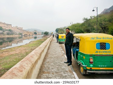 JAIPUR, INDIA - JAN 22: Handsome indian driver stand near the indian moto rickshaw & waiting for the passengers on the road on January, 22 2015. Jaipur, with populat. 6,664000, is capital of Rajasthan