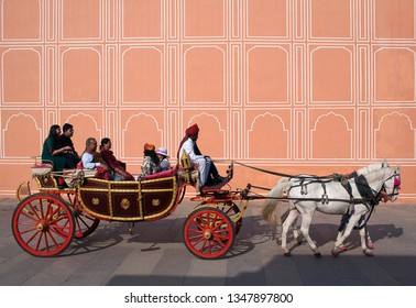 JAIPUR, INDIA - JANUARY 4, 2019: Happy Indian tourists riding a horse cart in famous Jaipur City Palace. Traditional animal usage for the transportation of tourists in Rajasthan state.