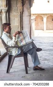 JAIPUR, INDIA - July 9, 2017 : Indian Man read newspaper at Chand Baori Stepwell in th village of Abhaneri, Rajasthan,Jaipur,INDIA