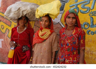 JAIPUR, INDIA - MARCH 08, 2006: Group of women carrying bags on a street in a neighborhood of Jaipur