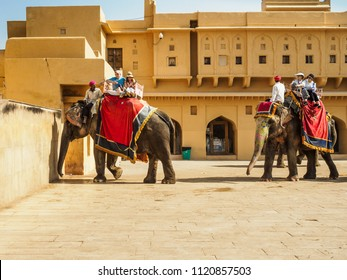 Jaipur, India - March 10, 2018: Western tourists riding the decorated elephants at Amber Fort in Jaipur city, Rajasthan State, India.