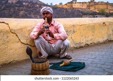 JAIPUR, INDIA -  MARCH 15, 2016 : Snake charmer sit and play music for demonstration of the cobra dance outside  Amber fort in Jaipur, India