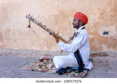 JAIPUR, INDIA - NOVEMBER 26, 2018 : Unidentified folk musician play on traditional music instrument called Kamaycha for tourists on the road on Amber Fort in the old city of Jaipur, Rajasthan, India