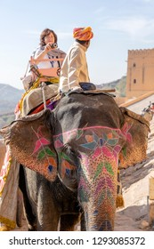 JAIPUR, INDIA - NOVEMBER 26, 2018 : Decorated elephants ride tourists on the road on Amber Fort in the old city of Jaipur, Rajasthan, India