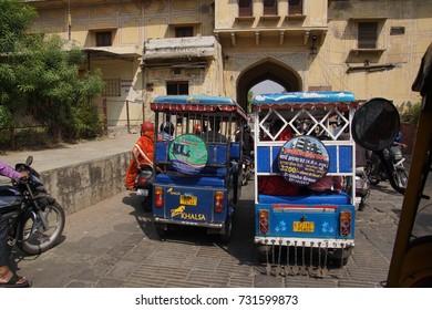 JAIPUR, INDIA - OCT 8, 2017 - Blue auto rickshaw tuktuks In traffic in  Jaipur, Rajasthan, India