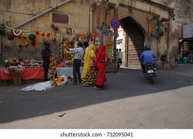 JAIPUR, INDIA - OCT 8, 2017 - Women in colorful saris  walking past Divali flower sellers in  Jaipur, Rajasthan, India