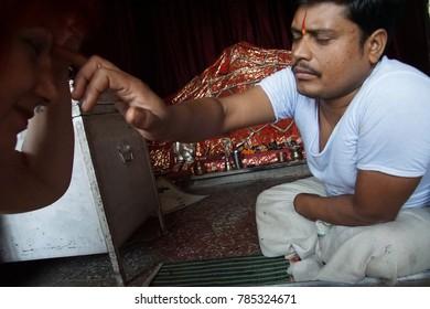 JAIPUR, INDIA - OCT 9, 2017 - Brahmin priest at altar of Galtaji temple, Jaipur, Rajasthan, India