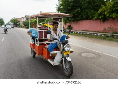 Jaipur, India - September 1, 2017: unidentified auto rickshaw or tuk tuk driver carrying passenger. This is the cheapest public transport in India.