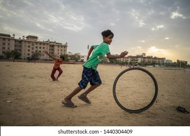 Jaipur, Rajasthan / India - 03 24 2019, Portrait of young children, Poor kids playing with a weel from bicycle in the slum area of the city