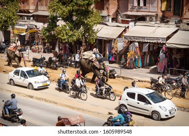 Jaipur, Rajasthan, India - 7 March 2012: Colorful painted elephants for the Holi Elephant festival riding through the busy traffic with bikes of the city center