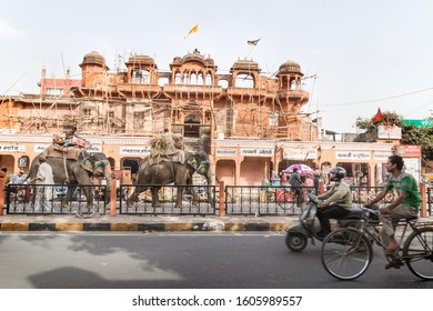 Jaipur, Rajasthan, India - 7 March 2012: Colorful painted elephants for the Holi Elephant festival riding through the busy traffic along a construction site of the city center