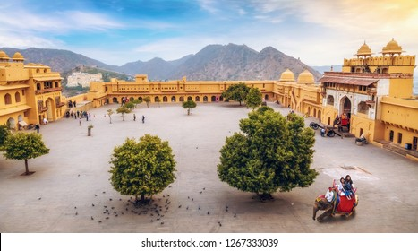 Jaipur, Rajasthan, India, December 11,2017: Aerial view of Amber Fort Jaipur, inner compound with view of tourists enjoying elephant ride at sunrise. Amer Fort is a UNESCO World Heritage site.