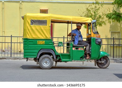 Jaipur, Rajasthan/ India - June 26 2019: Common Indian auto rickshaw in a city street of Jaipur with yellow background
