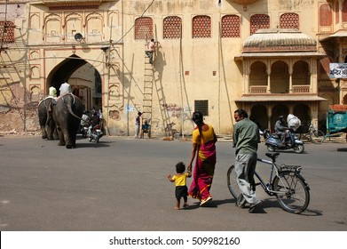 JAIPUR, RAJASTHAN, INDIA - MARCH 14, 2006: People, bicycles and elephants pass through the city center