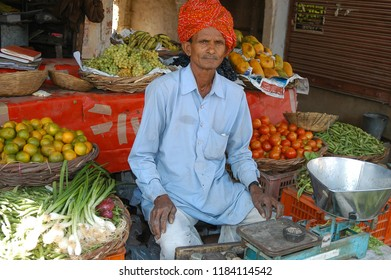 Jaipur, Rajasthan, India - march 24, 2006: Portrait of a turbaned merchant sitting inside a small vegetable and fruit stand in a central street in the village of Nayla Fort