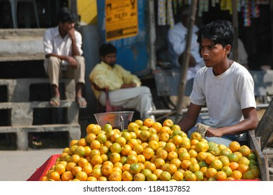 Jaipur, Rajasthan, India - march 24, 2006: Young man selling oranges on a cart in the street of a downtown suburb of the city of Jaipur, with blurred people in the background