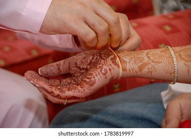 Jaipur, Rajasthan, India - May 27, 2011: Hands of brahman priest putting ritual thread on brides wrist with hands decorated with henna, during Hindu ceremony