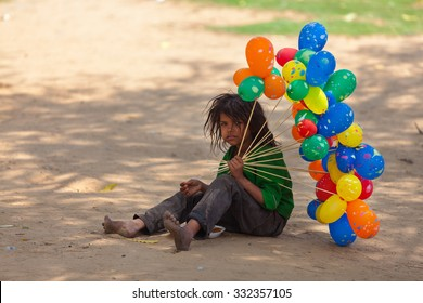 JAIPUR,INDIA - March 30, 2013 : Unidentified poor child tries to sell balloons and eats food that she can find in the streets of the city.
