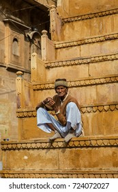 Jaisalmer, India - February 20, 2015: man without shoes on the steps of a temple in the old town of Jaisalmer