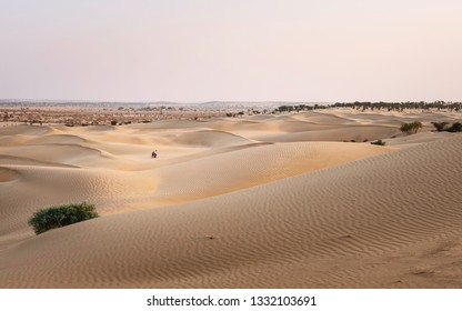 JAISALMER, INDIA - FEBRUARY 23, 2010: View across the sand dunes with a couple walking across the sand at dusk in summer on February 23, 2010 near Jaisalmer, Rajasthan, India.