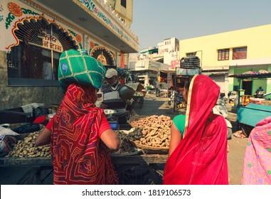 Jaisalmer, India - January 19, 2020 : Colourful saree on Indian women walking on crowed market in Jaisalmer, India