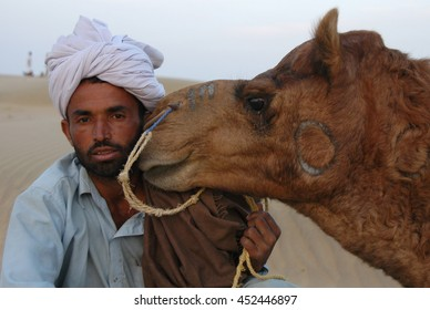 JAISALMER, INDIA - MARCH 20, 2006: A man with his camel in the desert of Thar
