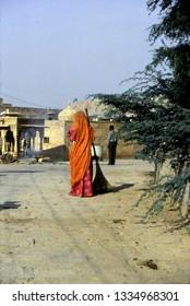 JAISALMER, INDIA - NOV 3, 2003 - Sweeper woman in bright colored saree outside Jaisalmer, India
