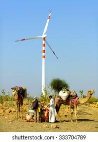 JAISALMER, INDIA-FEBRUARY 20: Unidentified people stand near wind turbine during safari on February 20, 2011 in Jaisalmer, India. Camel safaris in That desert are popular among tourists from Jaisalmer