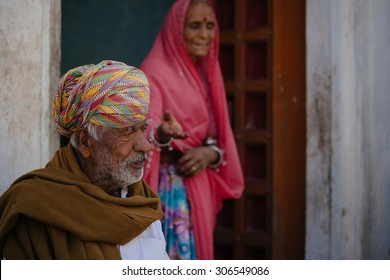JAISALMER - MARCH 22 : women and man posing in front of their house on March 22 , 2014 in Jaisalmer,India