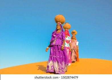 Jaisalmer, rajasthan, india - april 18th, 2018: women carrying heavy jugs of water on their head and walking on a yellow sand dune in the hot summer desert against blue sky.water crises