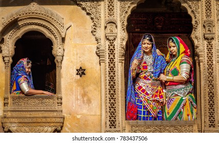 Jaisalmer, Rajasthan, India, December 14,2017: Indian women dressed in traditional Rajasthani outfit and jewelery pose at Patwon ki haveli heritage building Jaisalmer.
