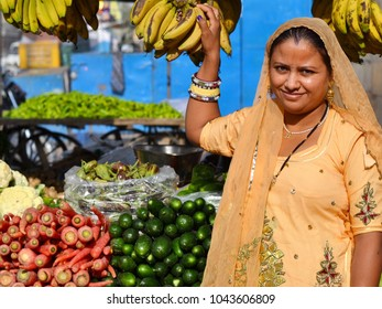 JAISALMER, RAJASTHAN / INDIA - MARCH 13, 2015: Rajasthani market woman, clad in a traditional sari, sells vegetables and bananas from her farm stall at the local market, on March 13, 2015.