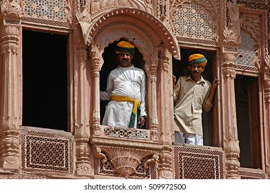 JAISALMER, RAJASTHAN, INDIA - MARCH 14, 2006: Men leaning out the windows of an old Haveli, in the city center
