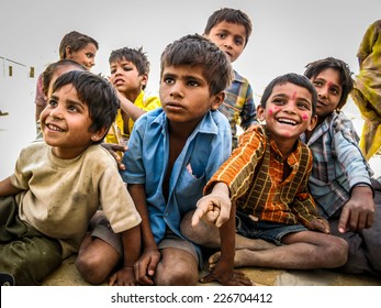 Jaisalmer, Rajasthan, India - March 27: Happy Indian children sitting out, smiling, at desert village in Jaisalmer, Rajasthan, India.