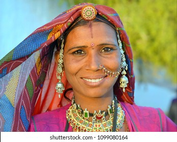 JAISALMER, RAJASTHAN / INDIA - MARCH 8, 2015: Rajasthani Gypsy woman in traditional tribal attire and jewelry (head jewelry, necklaces, nose jewelry) poses for the camera at sunset, on March 8, 2015.