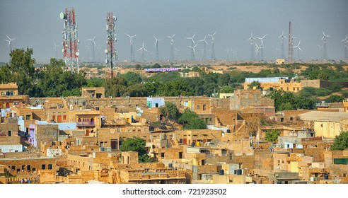 Jaisalmer, Rajasthan, India. Streets with cell towers and wind power generators in the background