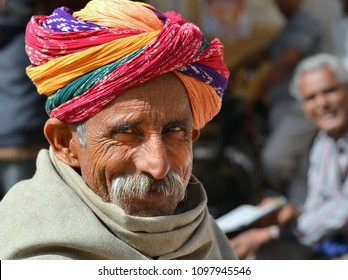 JAISALMER, RAJASTHAN/INDIA - MARCH 12, 2015: Elderly Indian man with moustache wears a colourful Rajasthani turban (pagari) and poses for the camera, on March 12, 2015.