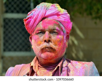 JAISALMER, RAJASTHAN/INDIA - MARCH 6, 2015: Elderly Indian man has his turban and face covered with pink color powder and poses for the camera during the Holi Festival of Colors, on March 6, 2015.